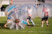 cinq personnes se foncent dedans en bubble foot sur un terrain extérieur