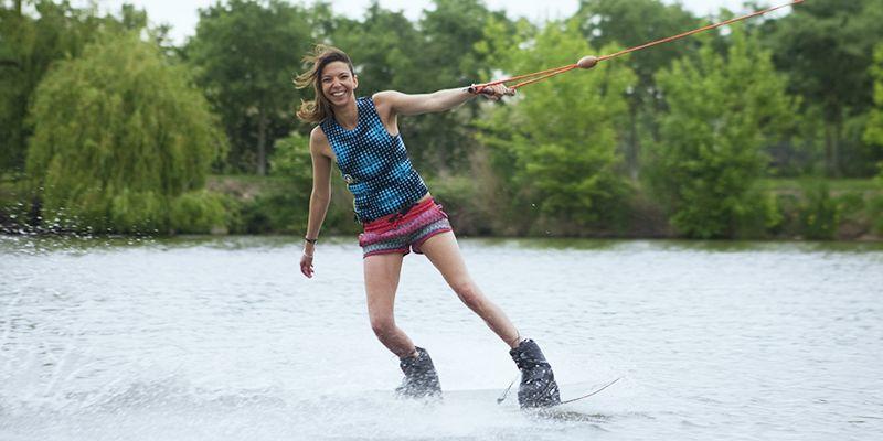 une femme sur une planche de wakeboard sur un lac de Toulouse