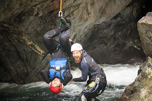 Une fille suspendu lors du canyoning en eau chaude