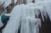 un homme escalade une cascade de glace