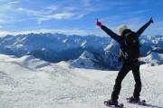 un homme lève les bras au sommet d'un mont en raquette à neige proche de Toulouse